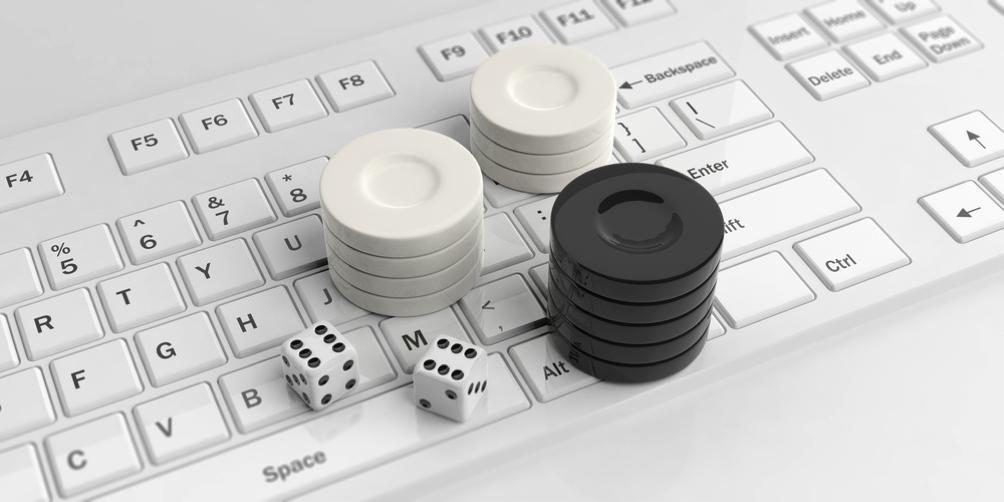 Ein Laptop, auf dessen Tastatur Würfel und Spielchips liegen.